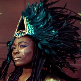 black lady in green and black feather jewelled head dress