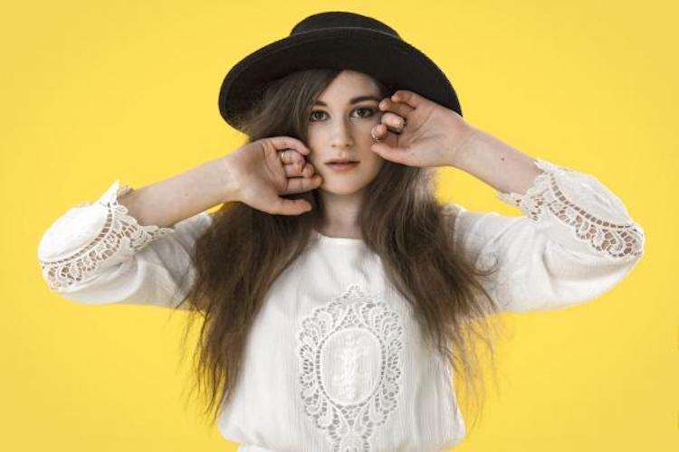 women in white lace top, black hat and yellow background