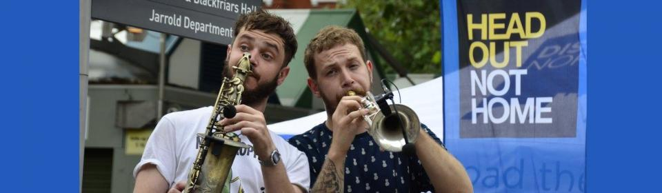 two men playing trumpets and saxophone