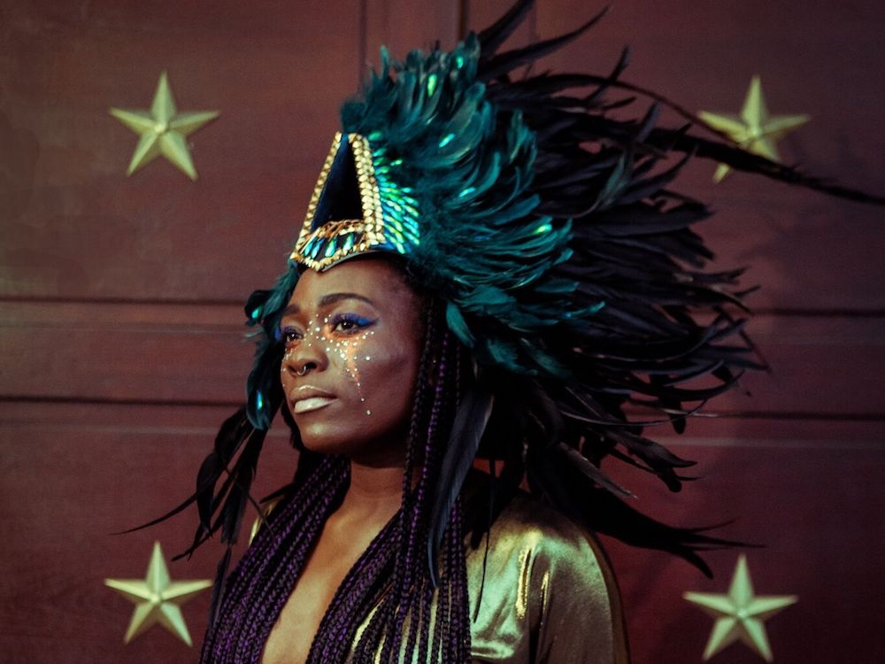 black lady with feather head dress and stars