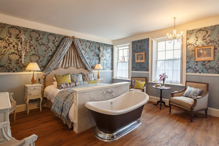 luxury bedroom with blue wallpaper and drapes with bath at the end of the bed