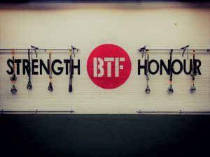 white wall with black text strength honour red BTF logo TRX straps hanging