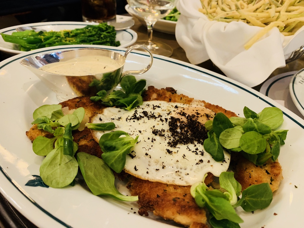 crumbed chicken breast spinach fried egg truffle shavings silver jug of white sauce