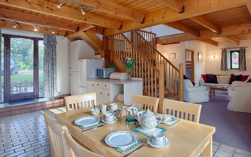 modern wooden cottage dining table laid with breakfast cutlery and plates wooden staircase in background