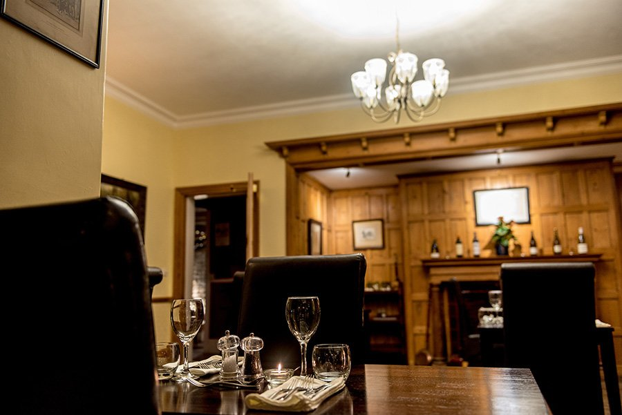 the grove guest house wood panelled dining room with dark leather chairs and wooden tables