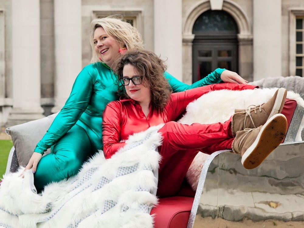 lady in green shiny lycra and another lady in red shiny lycra sat on a spa with fur blanket