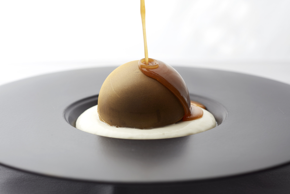 salted caramel pouring onto chocolate bombe