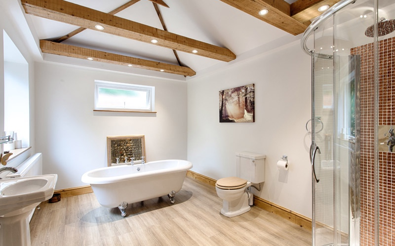 roll top bath wooden beams with spotlights wooden floor