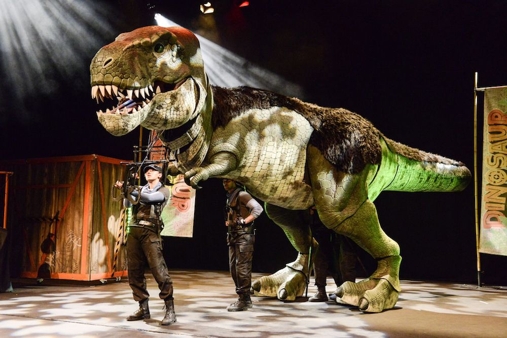 t-rex dinosaur on stage with a man