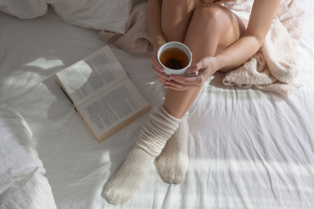 women sitting on bed with cup of coffee and book