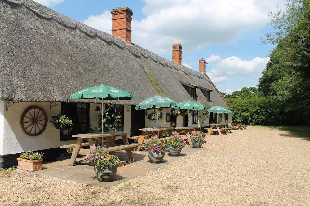 thatched rood long pub with bench style tables and green umbrellas