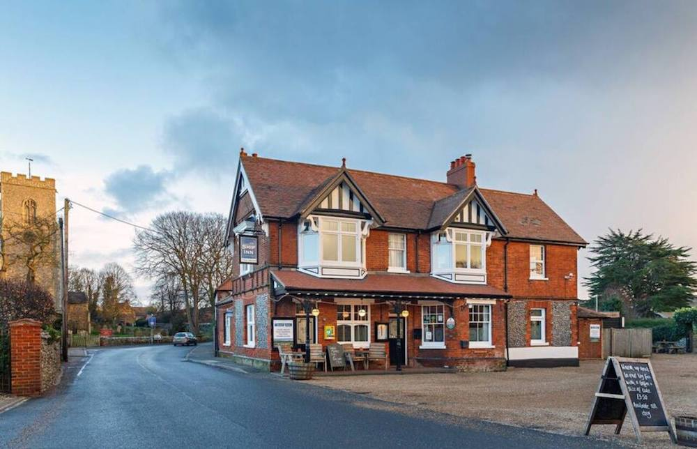 red brick pub with church spire in background