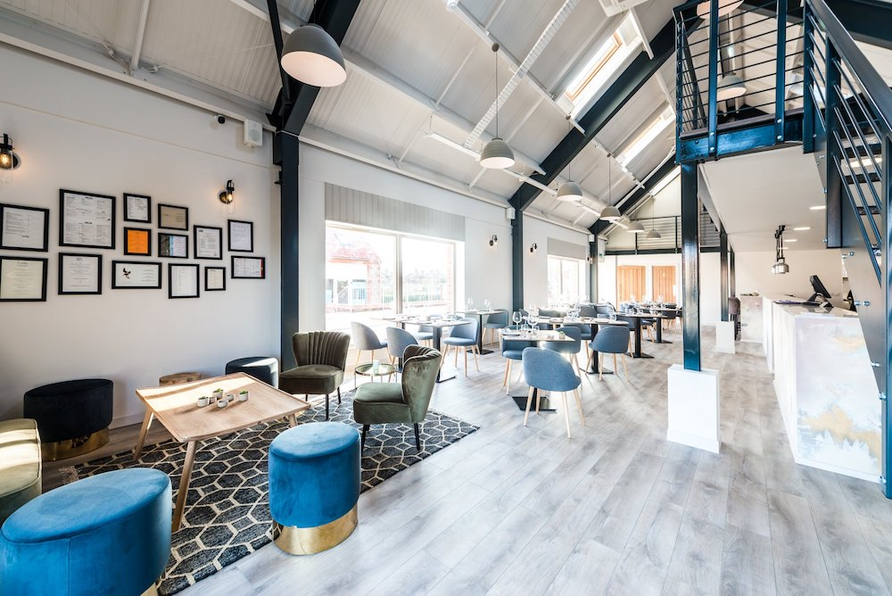 open plan restaurant grey floors blue stalls exposed metal beams