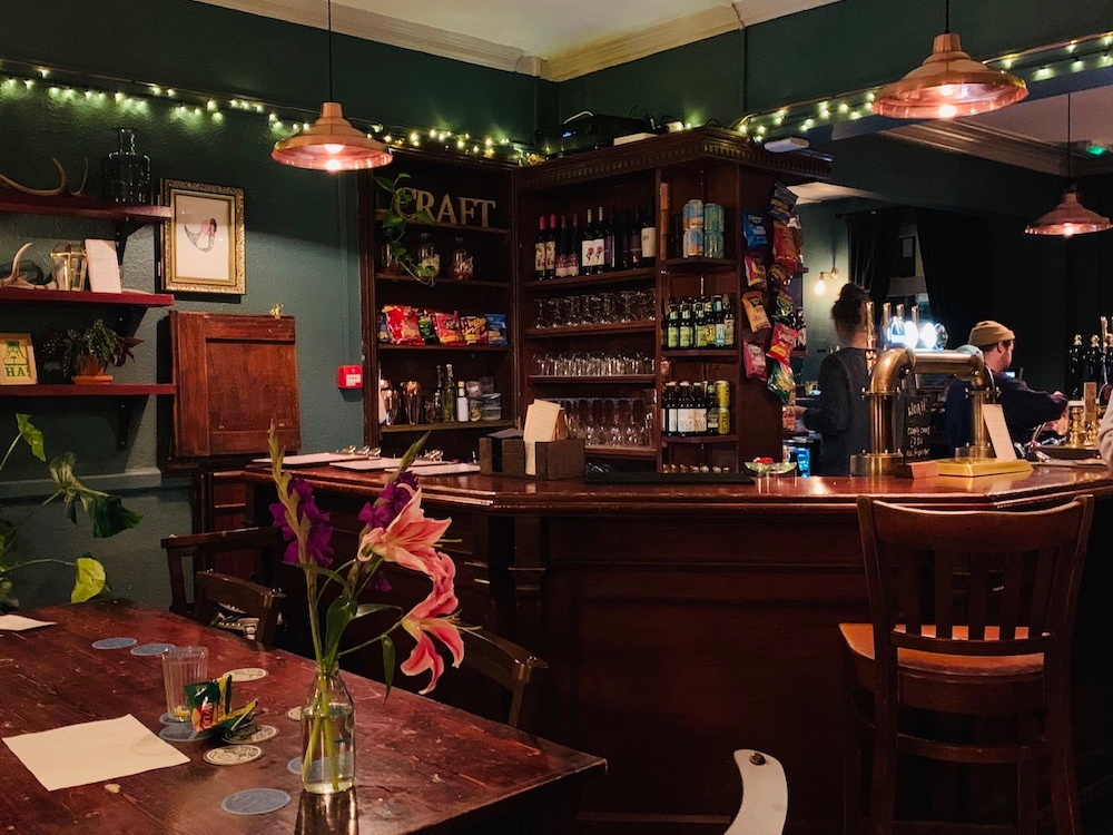 cosy dark wood bar with fairy lights shelves of wine a table with vase and pink flower
