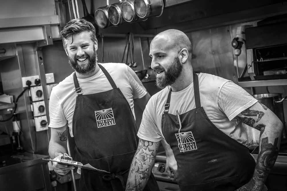 two chefs with aprons in a kitchen