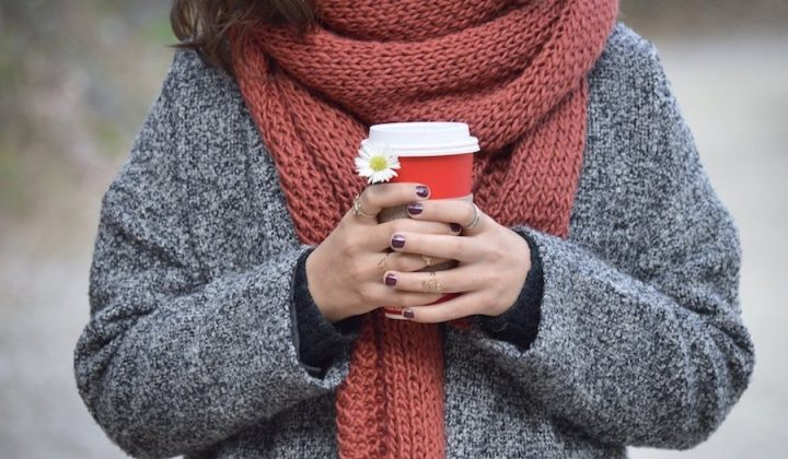lady in jumper holding a red coffee disposable coffee cup with a daisy big chunky orange scarf