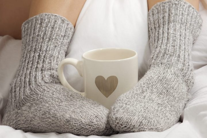 two cosy socks cuddling a mug with a gold heart on it