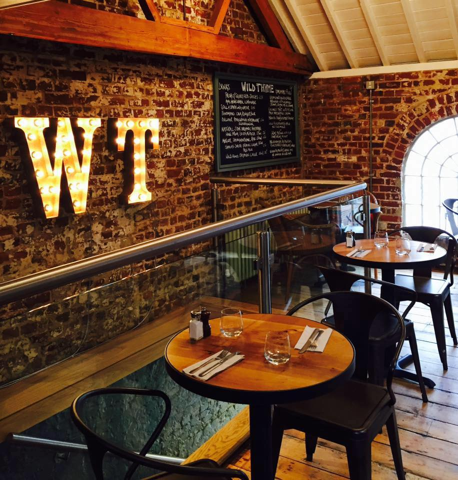 round tables and chairs restaurant exposed brick wall WT neon light sign
