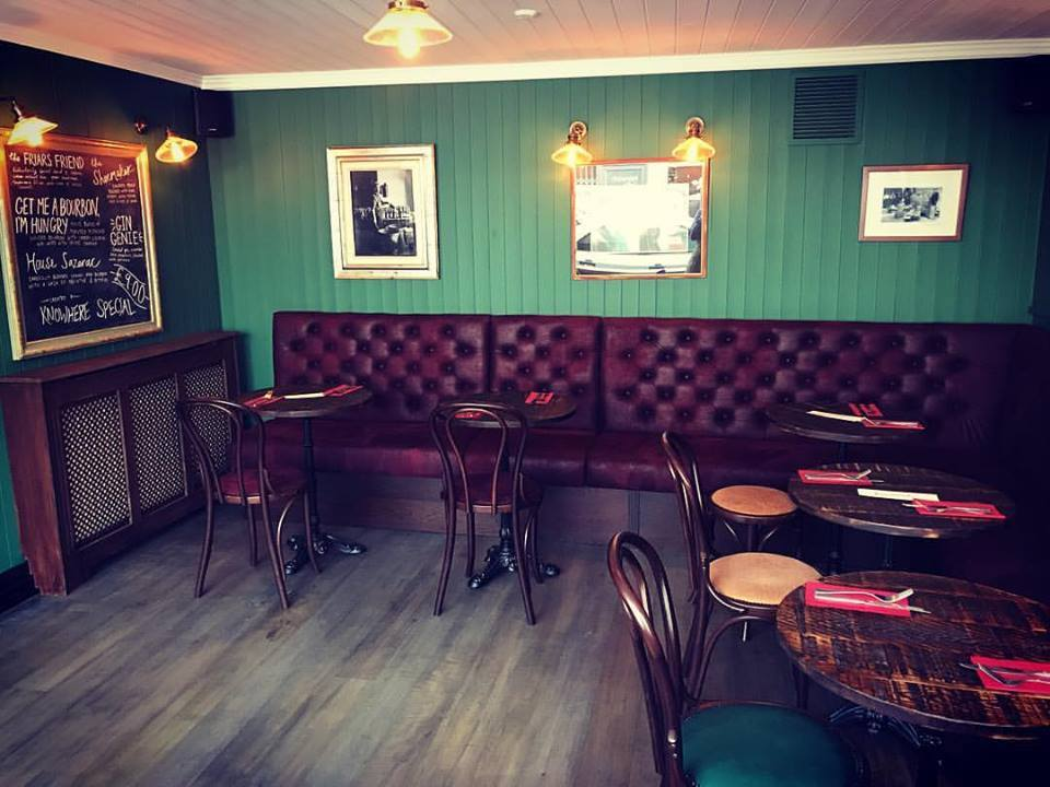 mahogany stud leather sofas, green walls, pictures on the wall wooden tables and chairs