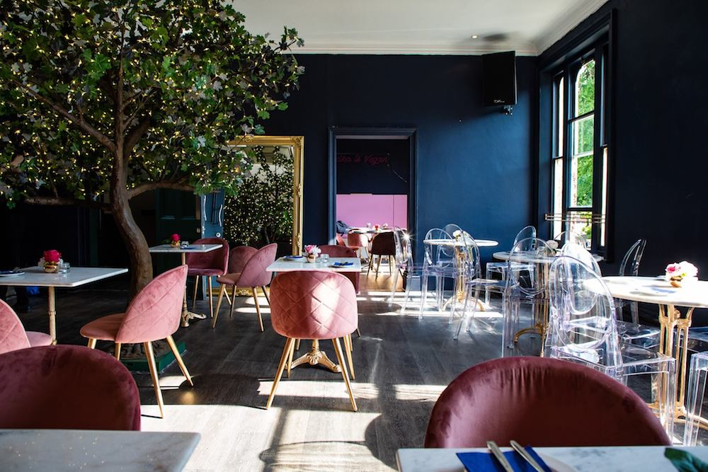 pink velvet chairs white tables dark blue wall tree in middle of restaurant