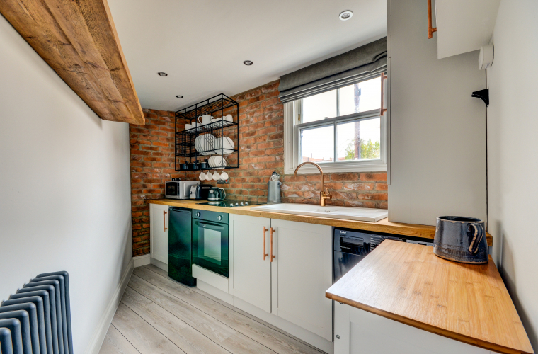modern white kitchen wooden work stops exposed brick wall
