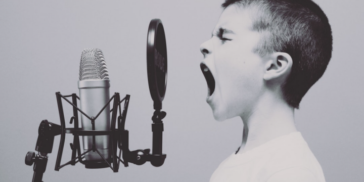 black and white image of a young boy shouting into a microphone
