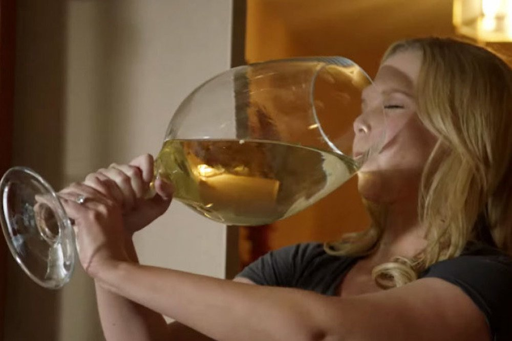 lady drinking a huge glass of white wine