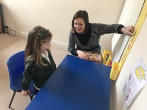 young girl playing a board game with a therapist