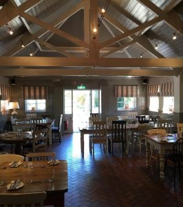high ceiling conservatory, beams, tables and chairs