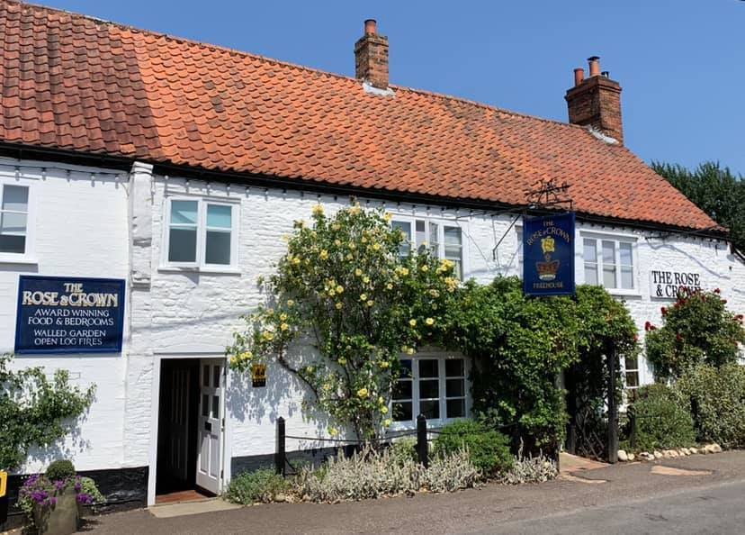white washed pub with roses around the door