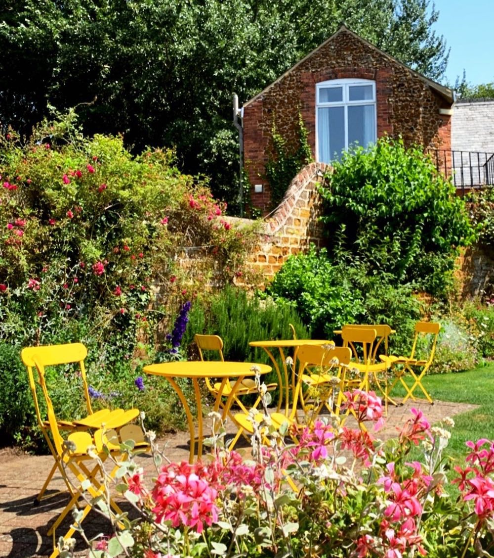 lush green garden, pink flowers, yellow table and chairs