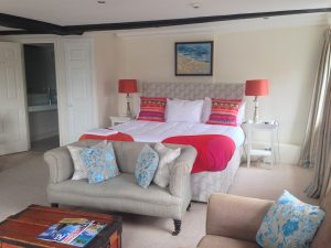 hotel bedroom with bed, sofas, bright cushions