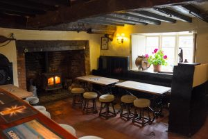 beamed ceiling bar with wood burner in ingle nook fireplace