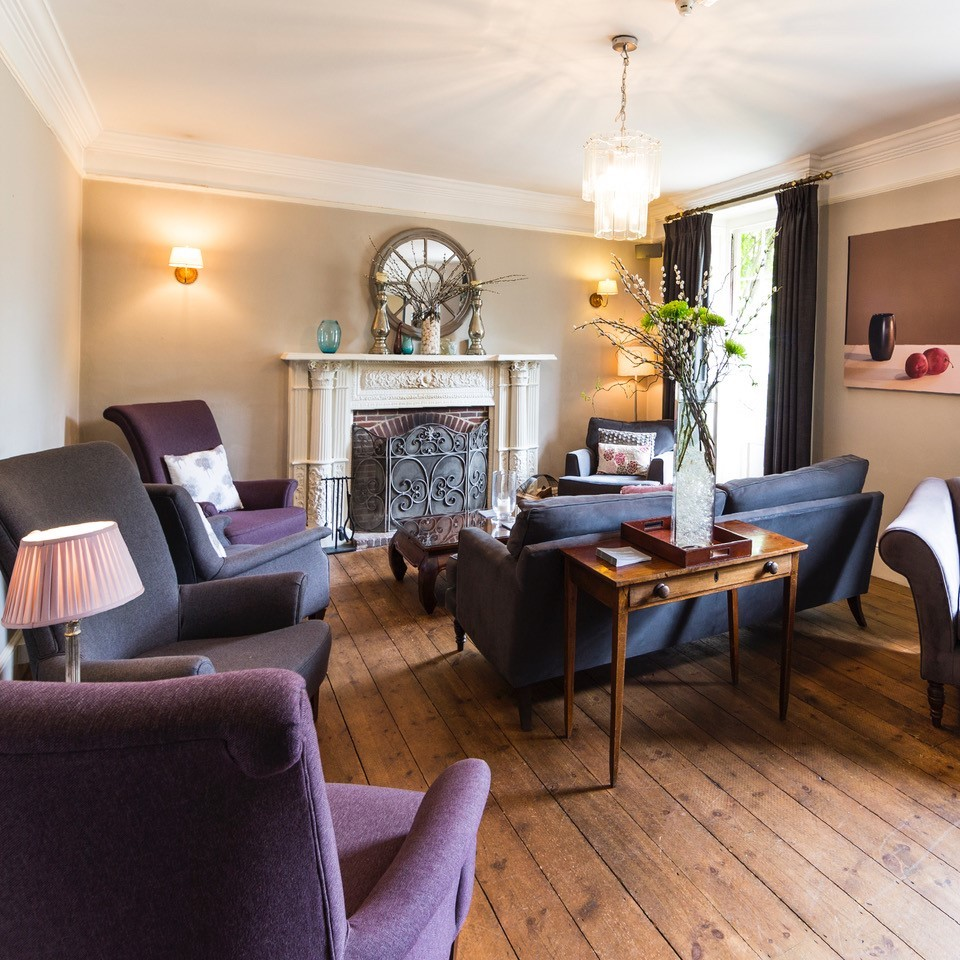 lounge room with purple high back chairs wooden floors and fire place