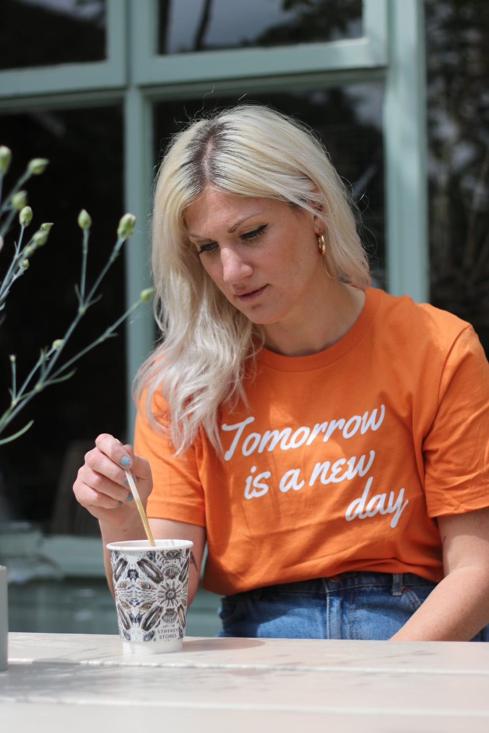 Lady wearing an orange t-shirt which says tomorrow is another day