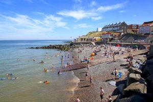 sheringham beach with people sunbathing and swimming in the sea